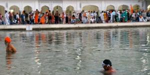 Sikh pilgrims bathe in the Amrit Sarovar